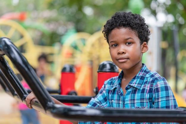 Menino americano africano, olhar câmera, enquanto, exercício, parque infantil, parque