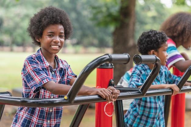 Menino americano africano, sorrindo, olhar câmera, enquanto, exercício, parque infantil, parque