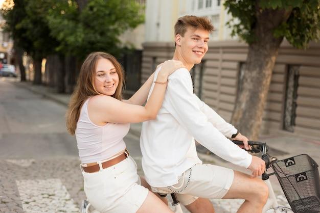 Menino andando de bicicleta com a namorada