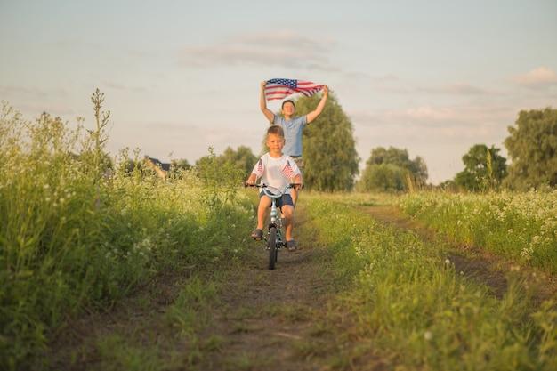 Menino andando de bicicleta em 4 de julho com o vento no campo verde