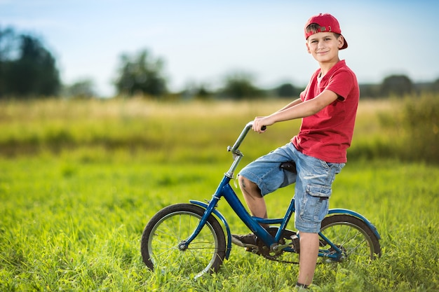 Menino andando de bicicleta em um campo