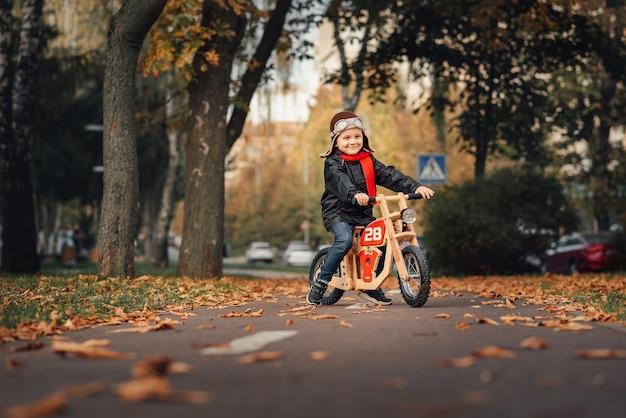 Menino andando de bicicleta na cidade no outono Foto Premium