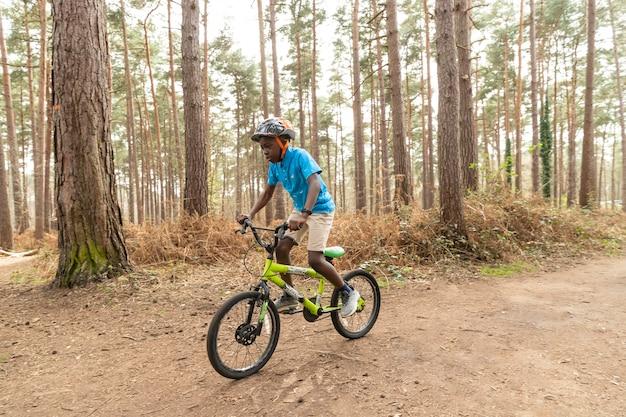 Menino andando de bicicleta na floresta
