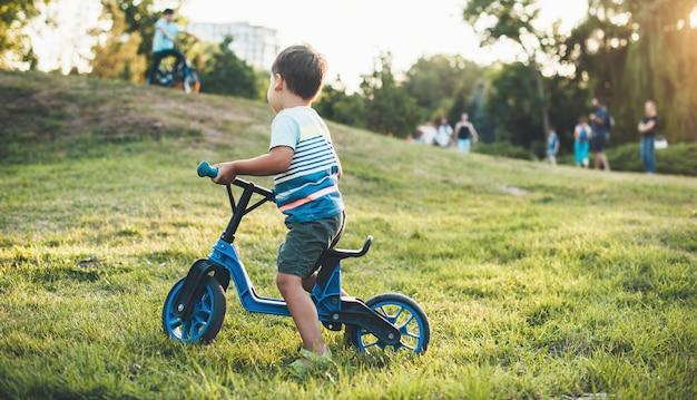 Menino andando de bicicleta no parque olhando outras crianças caminhando com os pais