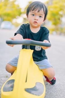 Menino andando de trycycles. menino asiático cavalgando tolocar no quintal. Foto Premium