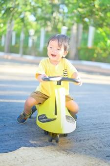Menino andando de trycycles. menino asiático cavalgando tolocar no quintal.