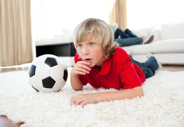 Menino animado assistindo jogo de futebol deitado no chão