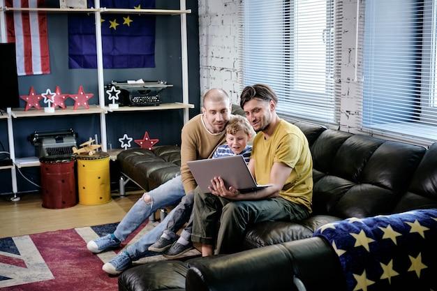 Menino animado e seus dois pais assistindo a um filme interessante ou desenho animado no laptop quando passam o fim de semana em casa