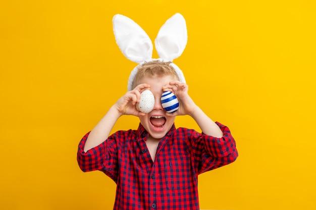 Menino animado em orelhas de coelho coelho na cabeça e ovos de páscoa nos olhos sobre amarelo