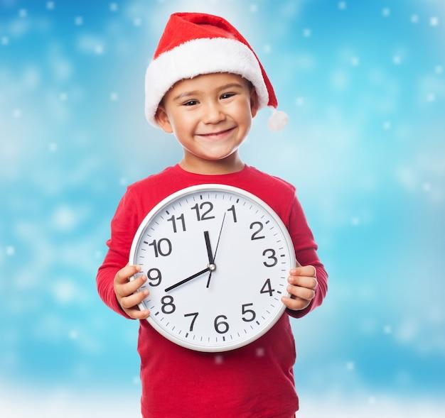 Menino animado mostrando um relógio branco