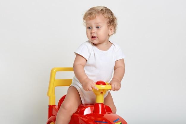 Menino animado sentado em um tolocar vermelho e amarelo, desviando o olhar com interesse, vestindo macacão branco