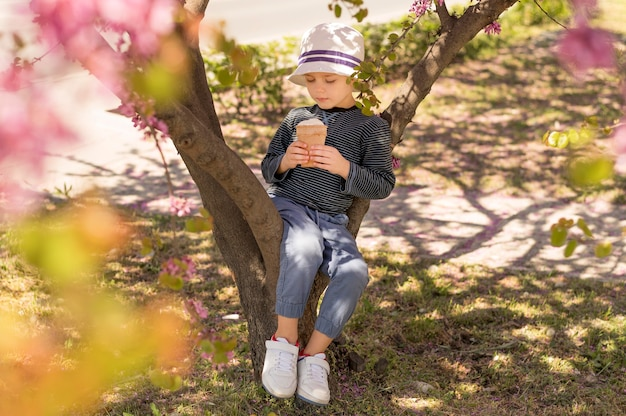 Menino ao ar livre, sentado na árvore