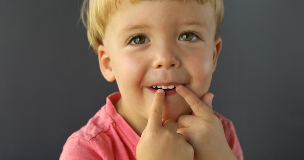 Menino aponta os dedos das duas mãos nos dentes