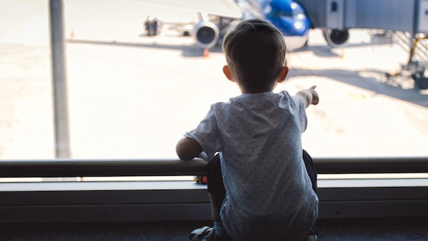 Menino apontando com o dedo no avião no aeroporto.