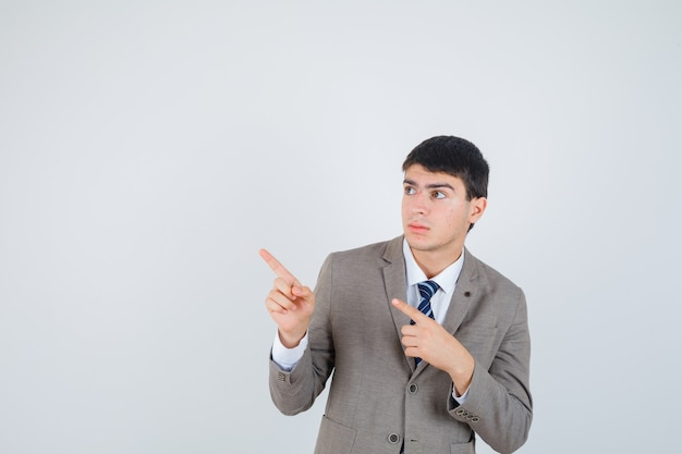 Menino apontando para a esquerda com o dedo indicador em um terno formal e olhando sério, vista frontal.