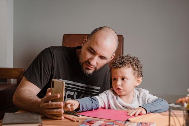 Menino apontando para o celular do pai enquanto fazia os trabalhos da escola