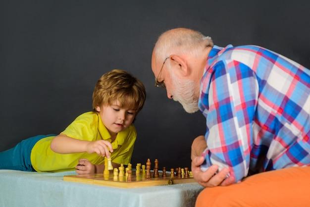 Menino aprendendo a jogar xadrez e atividades para crianças, avô e neto, jogando