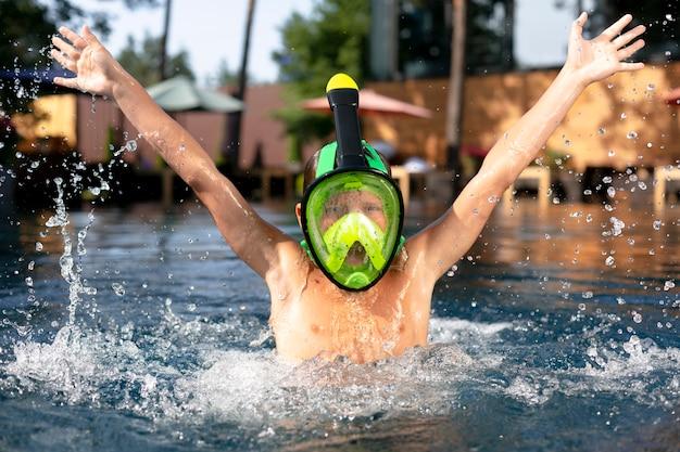 Menino aproveitando o dia na piscina com máscara de mergulho