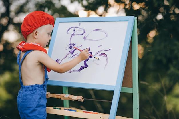 Menino artista desenhando no parque ao pôr do sol
