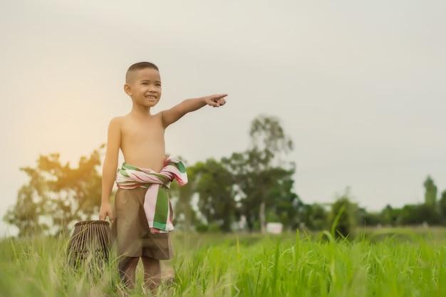 Menino asiático a pescar durante os feriados no campo de exploração agrícola verde no verão, tailândia.