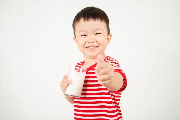 Menino asiático, bebendo leite de vidro com sorriso no rosto