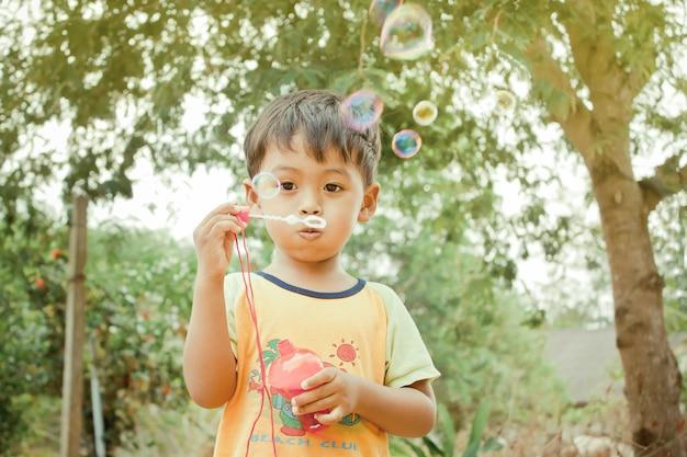 Menino asiático brincando com varinha de bolha, soprando bolhas de sabão