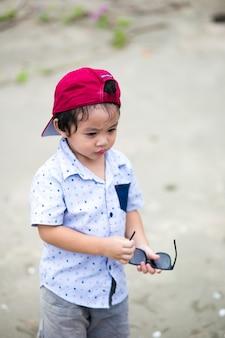 Menino asiático caminhando na praia tropical, menino feliz caminhando perto do mar