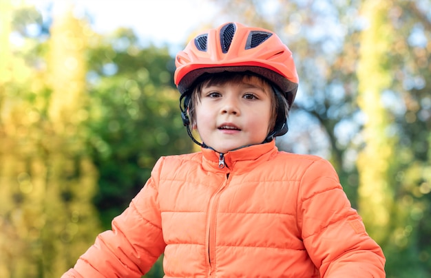 Menino asiático-caucasiano de 6 a 7 anos de idade, mestiço, usa um capacete de bicicleta, parado do lado de fora no parque