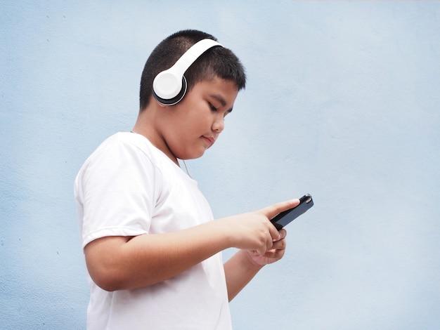 Menino asiático com camisa branca, usando fones de ouvido e jogando o telefone móvel sobre o fundo da parede azul.