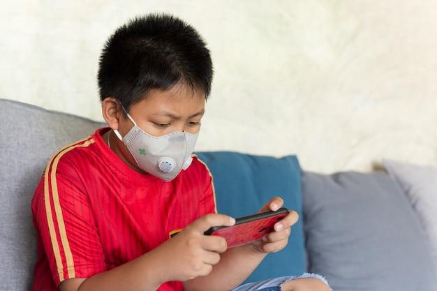 Menino asiático com máscara protetora, jogando o jogo no celular em casa.
