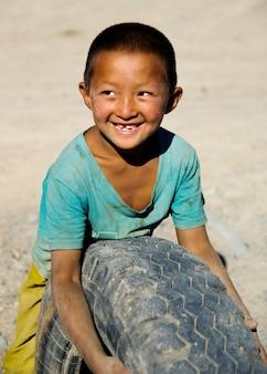 Menino asiático com um sorriso bonito que joga com um pneu.