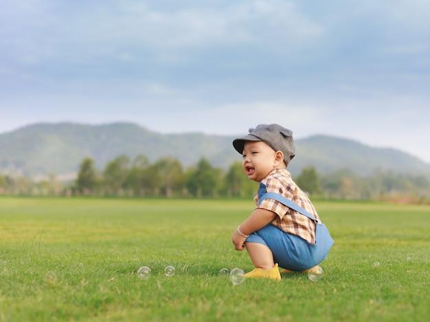 Menino asiático da criança brincando no parque natural