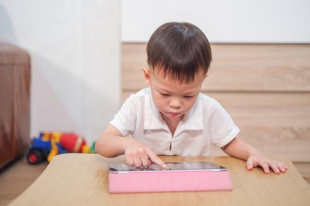 Menino asiático da criança de 2 - 3 anos de idade, usando o tablet pc, jogando o jogo, assistindo a um vídeo do tablet pc. garoto viciado em gadgets