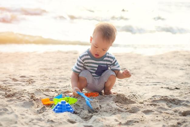 Menino asiático da criança que senta-se & que joga os brinquedos da praia das crianças na praia do por do sol tropical arenosa bonita