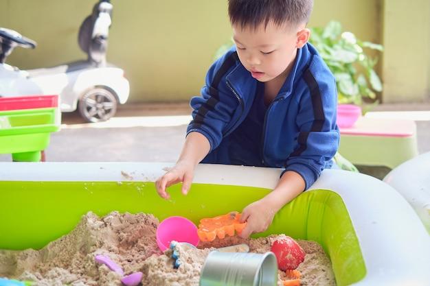 Menino asiático de 5 anos brincando com areia em casa, criança brincando com brinquedos de areia, educação montessori