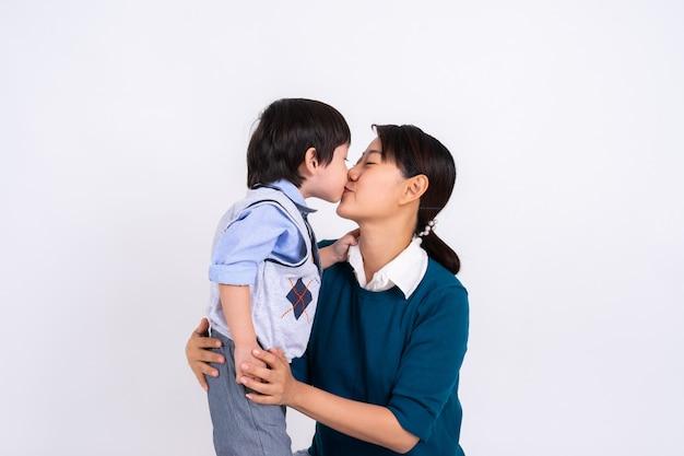 Menino asiático de retrato beijando sua mãe com amor