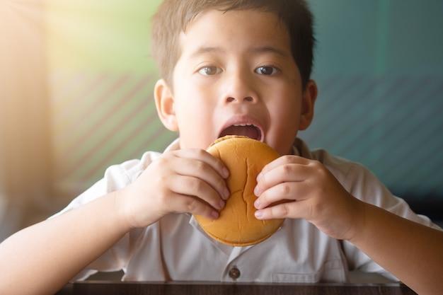 Menino asiático do retrato que come um hamburger. conceito de saúde.