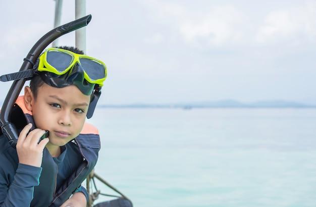 Menino asiático do retrato que veste um colete salva-vidas e um mar do fundo do mergulho autônomo.