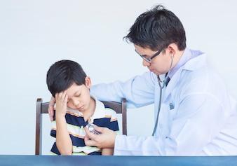 Menino asiático doente sendo examinado pelo médico sobre fundo branco