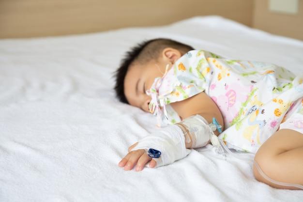 Menino asiático, dormindo na cama com infusão definida no departamento de crianças no hospital