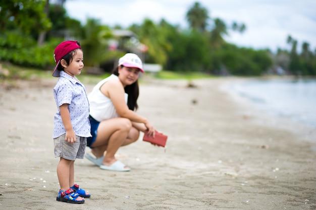 Menino asiático e mãe caminhando na praia tropical, menino feliz caminhando perto do mar