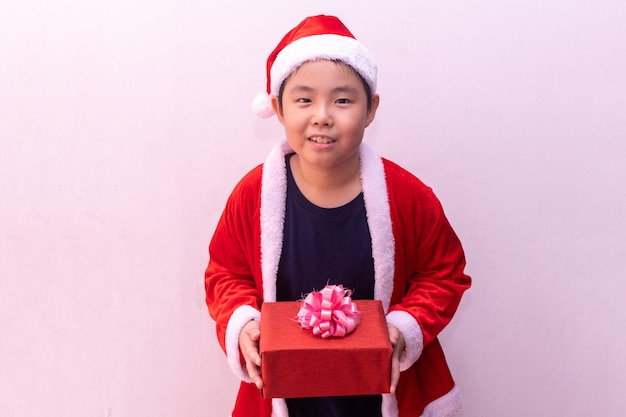 Menino asiático, em, papai noel, roupas, segurando, presente