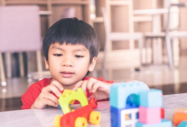 Menino asiático, empilhando blocos brinquedo, ligado, um, sala de estar, tabela