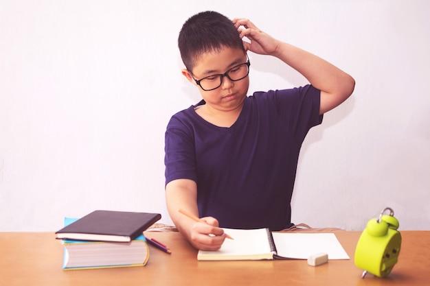 Menino asiático estudante entediado e cansado fazendo lição de casa