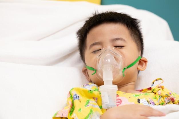 Menino asiático fazendo inalação com nebulizador no hospital.