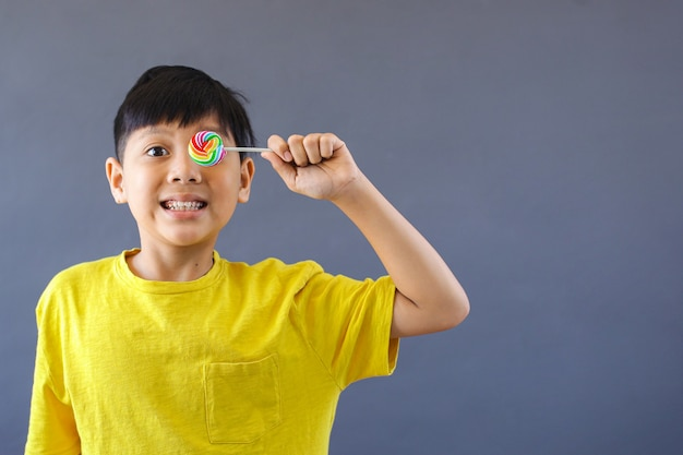 Menino asiático feliz segurando pirulito