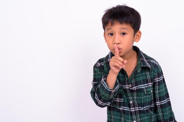 Menino asiático fofo vestindo uma camisa xadrez verde encostada na parede branca