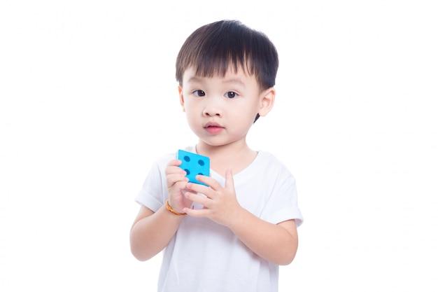Menino asiático jogando brinquedo e olhando para a câmera sobre fundo branco