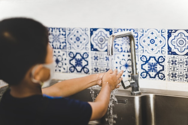 Menino asiático lavando as mãos com água da torneira na pia da cozinha durante covid-19.