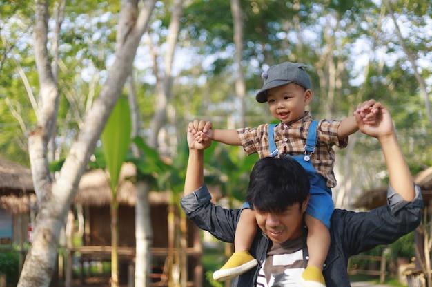 Menino asiático, montando, pescoço pai